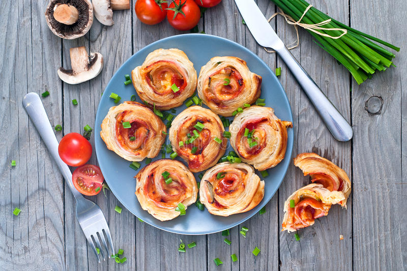 Puff pastry rolls with ham and chese. Baked snacks stock images