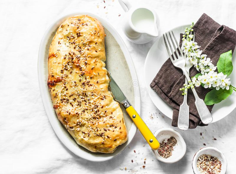 Puff pastry savoury strudel with cabbage, broccoli and mozzarella cheese served on a white table, top view stock photos