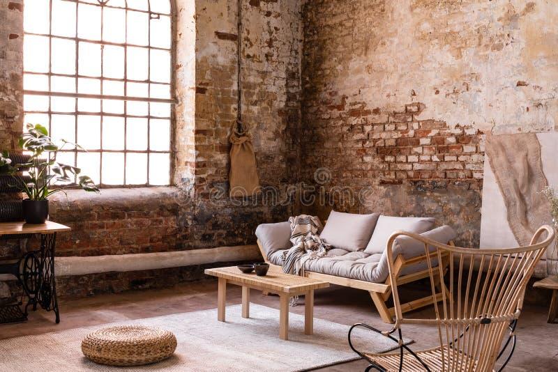 Puff und Holztisch auf Teppich nahe Fenster in wabi sabi Innenraum mit Sofa und Lehnsessel lizenzfreies stockbild