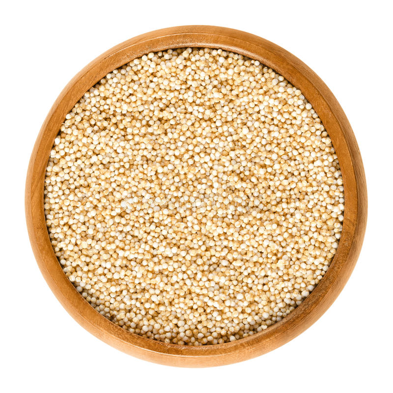Puffed amaranth in wooden bowl over white. Puffed amaranth in wooden bowl. Popped grains of Amaranthus. Pseudocereal and rediscovered healthy staple food of the stock photos