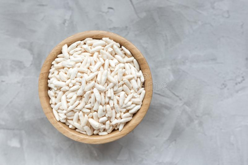 Puffed rice in a wooden bowl on a gray background royalty free stock photography