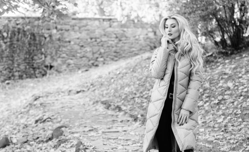Puffer jacket casual and comfortable style. Girl fashionable blonde walk in autumn park. Woman wear warm grey jacket stock photo