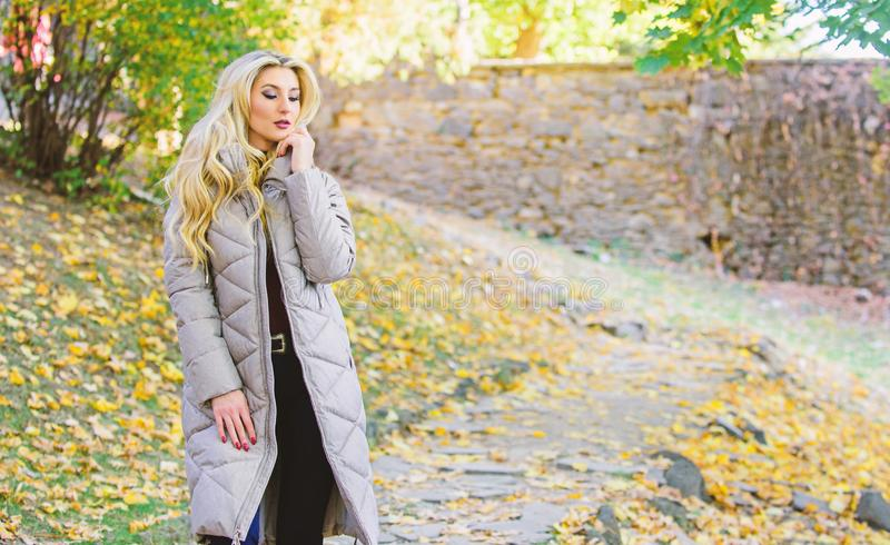 Puffer jacket casual and comfortable style. Girl fashionable blonde walk in autumn park. Woman wear warm grey jacket. Jacket everyone should have. Puffer stock images