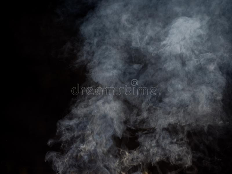 Puffs of white smoke in blurred dynamics on a dark background. Studio photography stock photos