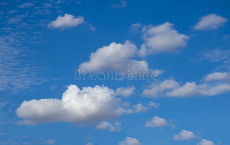Puffy cloudy blue sky background. Cloudy blue sky taken on a summers day suitable for backgrounds stock images