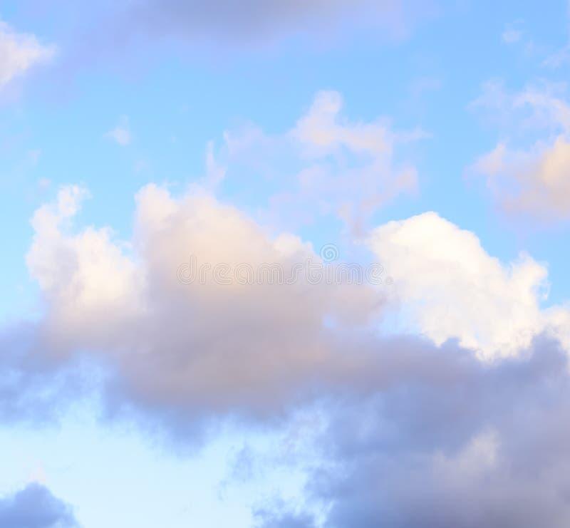 Puffy nuvens contra fundo azul-céu imagem de stock
