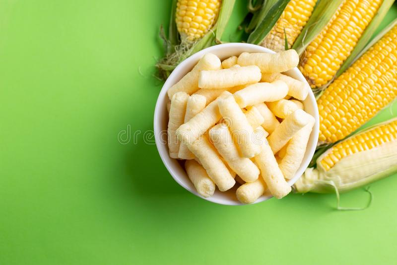 Pufuleti και φρέσκα σιτάρια του ώριμου καλαμποκιού, πέρα από το πράσινο υπόβαθρο στοκ φωτογραφία με δικαίωμα ελεύθερης χρήσης