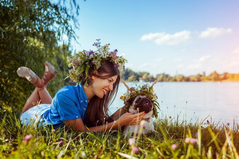 Pug dog and its master chilling by river wearing flower wreaths. Happy puppy and woman enjoying summer nature outdoors stock photography