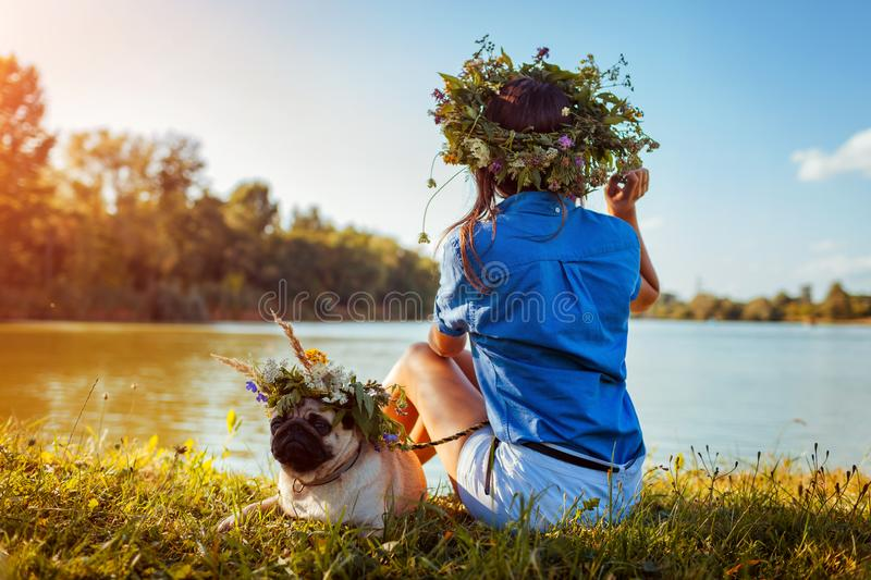 Pug dog and its master chilling by river wearing flower wreaths. Happy puppy and woman enjoying summer nature outdoors royalty free stock images