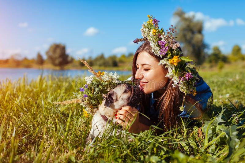 Pug dog and its master chilling by summer river wearing flower wreaths. Happy puppy licking woman stock photo