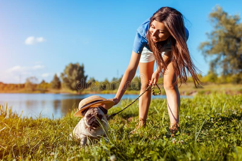 Pug dog sitting by river while woman puts hat on it. Happy puppy and its master walking and chilling outdoors royalty free stock photo