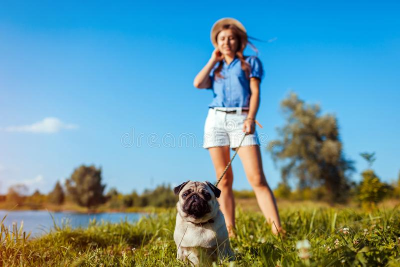 Pug hondzitting door rivier Gelukkig puppy die een bevel van meester wachten Hond en vrouw die in openlucht koelen royalty-vrije stock fotografie