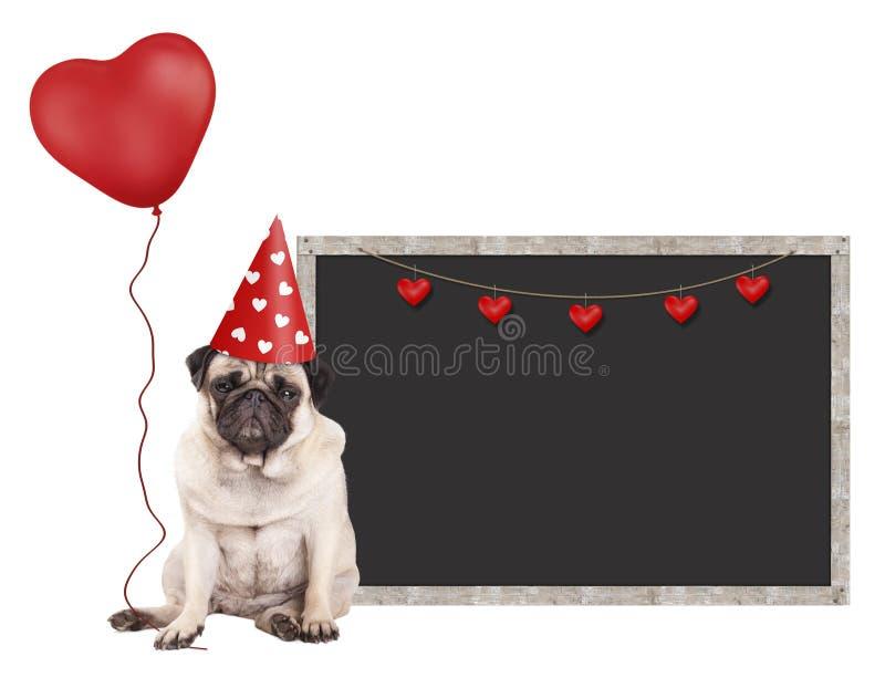 Pug puppyhond met rode partijhoed die, die naast leeg bordteken zitten en hart gevormde die ballon houden, op witte B wordt geïso royalty-vrije stock afbeeldingen