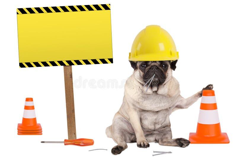 Pughund mit gelbem Erbauerarbeitskraftschutzhelm und -kegel, plus Warnzeichen auf hölzernem Pfosten lizenzfreie stockfotos