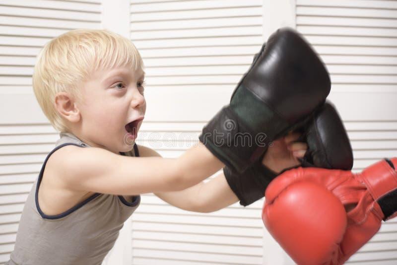 Pugilato biondo del ragazzo con la mano in guanto rosso emozioni fotografia stock libera da diritti