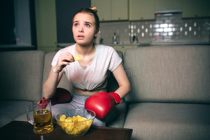 Pugilato di orologio della giovane donna sulla TV alla notte La bionda stupita cerca e mangia gli alimenti industriali Sorveglian fotografia stock
