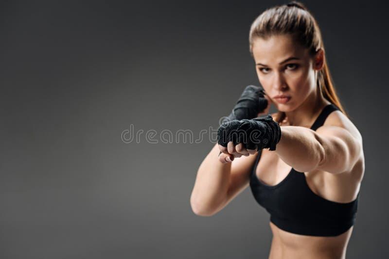 Pugilato potente della donna su un fondo grigio fotografia stock