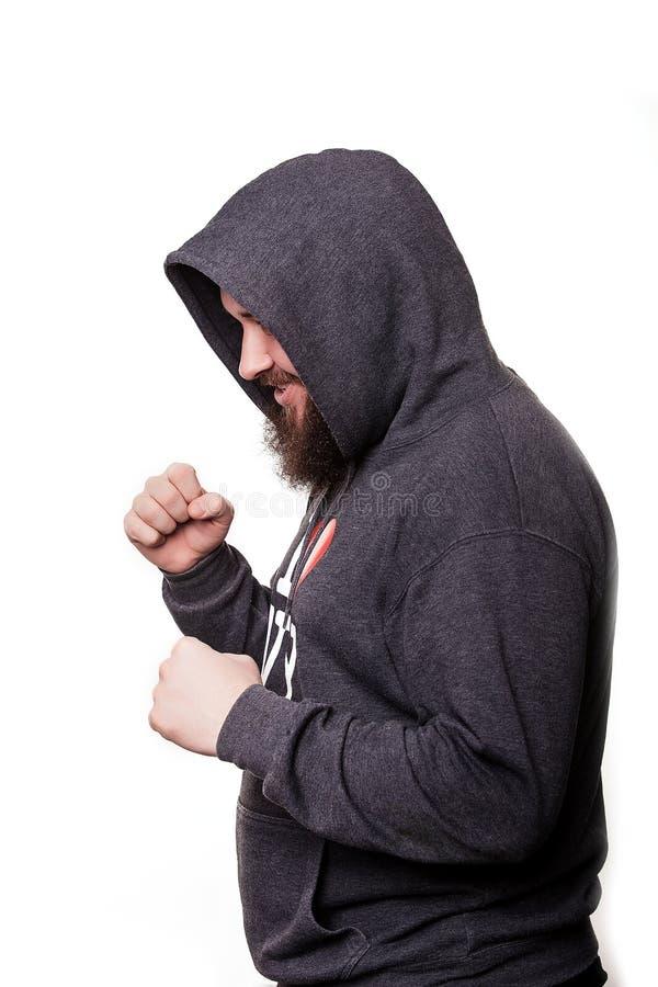 Pugile con un fronte serio con una barba nel cappuccio nell'addestramento Isolato su priorità bassa bianca immagini stock libere da diritti