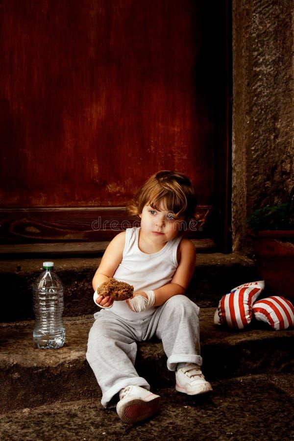 Pugile del bambino che si siede sui punti con un pezzo di pane nella mano fotografia stock libera da diritti