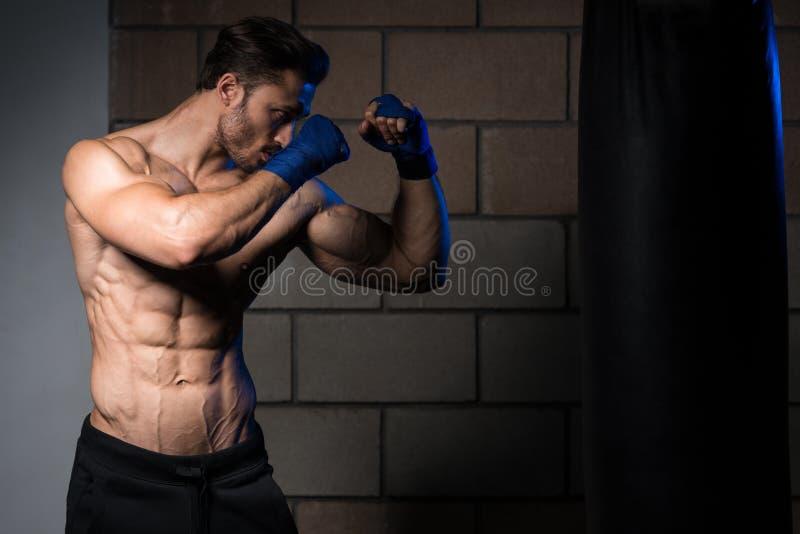 Pugilista muscular descamisado com o saco de perfuração no gym imagem de stock