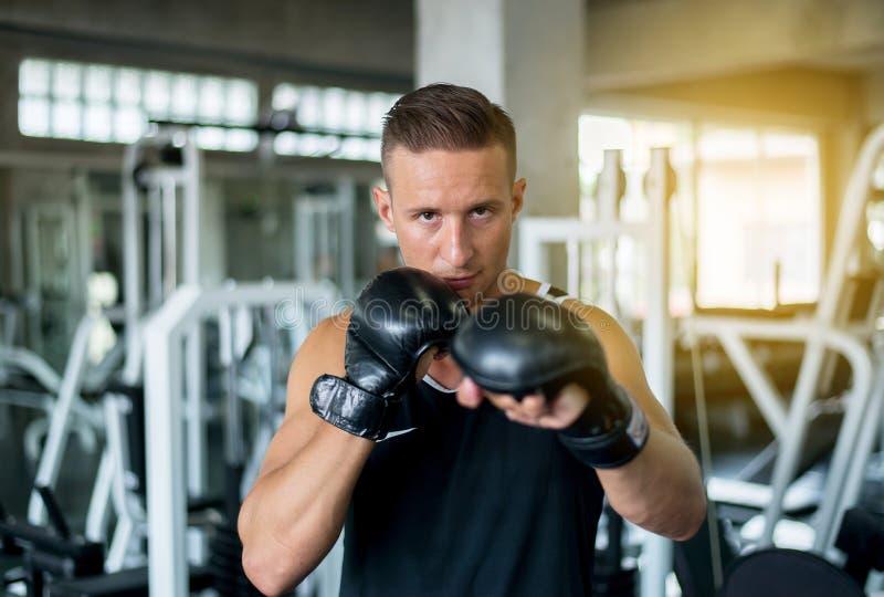 Pugilista que perfura em um gym de encaixotamento, treinamento do homem do pugilista dos homens no saco de perfuração fotografia de stock