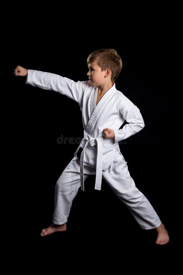 Pugno chiuso colpito nel karatè Bambino serio in kimono nuovissimo su fondo nero immagine stock