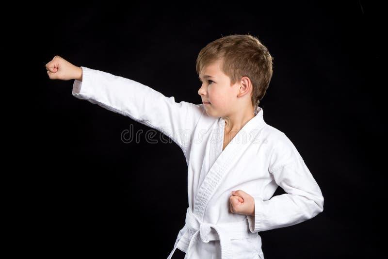 Pugno chiuso colpito nel karatè, macro Bambino serio in kimono nuovissimo su fondo nero fotografia stock libera da diritti