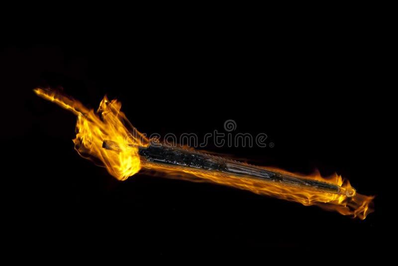 Pugno del fuoco e spada di vetro fotografia stock