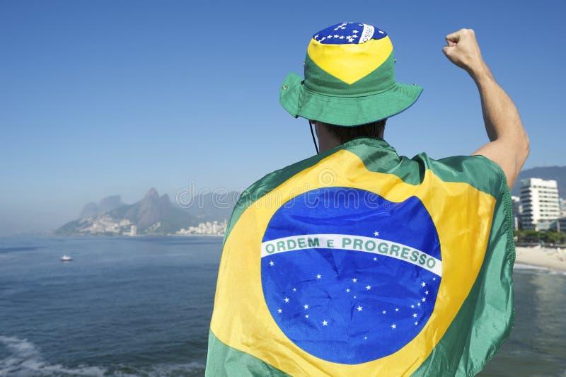 Pugno di pompaggio dell'uomo brasiliano con la bandiera Rio Skyline fotografia stock