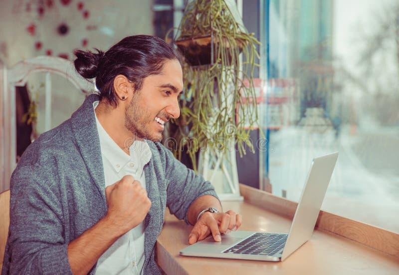 Pugno di pompaggio dell'uomo euforico mentre esaminando il computer portatile fotografie stock