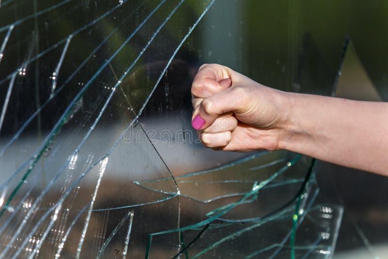 Pugno femminile che frena la finestra di vetro fotografia stock
