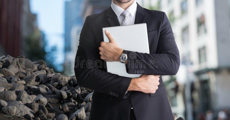 Puinstenen in stad met laptop van de zakenmanholding stock fotografie