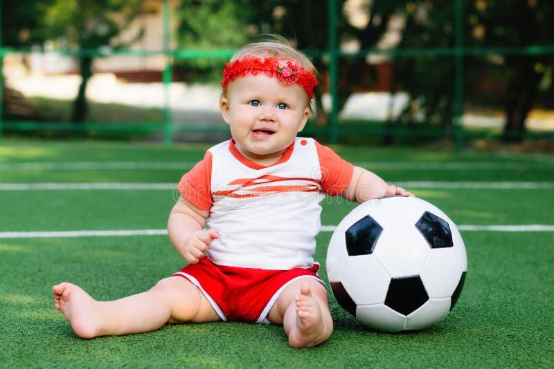 Puissance de fille : Peu fille blonde dans le stade jouant avec une boule du football images libres de droits