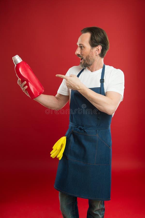 Puissance de nettoyage impressionnante Homme mûr se dirigeant à la bouteille détersive Homme supérieur dans le tablier prêt pour  photo stock