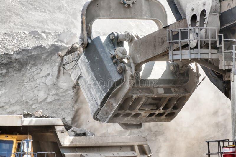 Puissant et grand godet de pelle Chargement de minéraux dans le corps d'un camion d'extraction images libres de droits