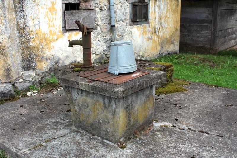 Puits concret avec la couverture rouillée en métal et le seau gris verrouillés avec le cadenas à côté de la vieille pompe à eau c images libres de droits