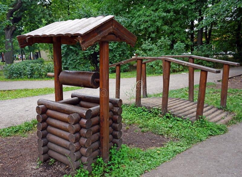 Puits décoratif et un petit pont en parc de ville photos stock