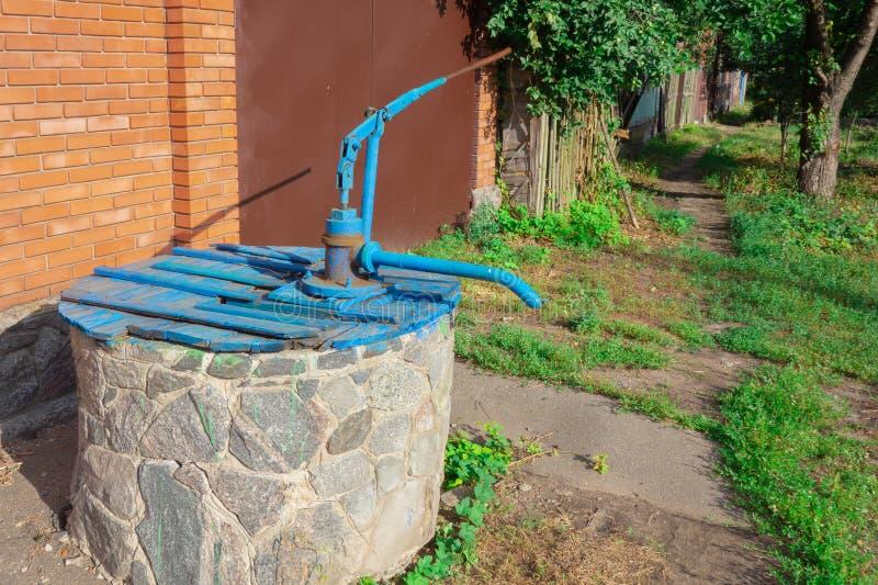 Puits d'eau du comté de village de ferme avec la pompe manuelle de main Vieux équipements de service d'approvisionnement Image de photographie stock