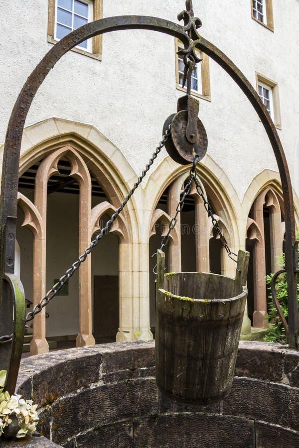Puits d'eau et un seau dans l'ancien cloître de l'église Trinitarian dans Vianden, Luxembourg images libres de droits