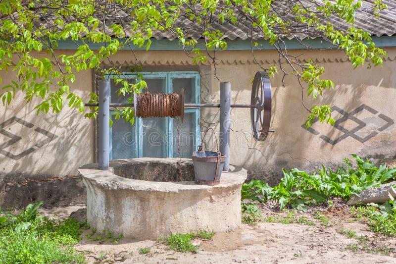 Puits d'eau rural près de maison image stock