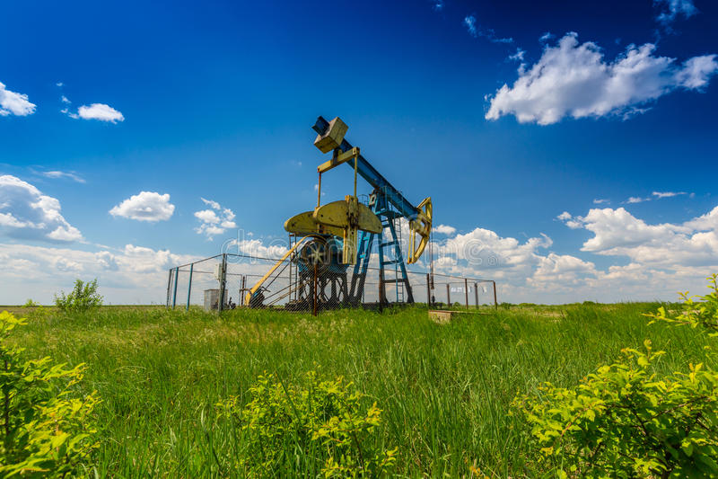 Puits de pétrole et de gaz profilé sur le ciel bleu avec des cumulus, en Europe images stock