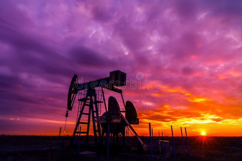 Puits fonctionnant de pétrole et de gaz et ciel de coucher du soleil photo libre de droits