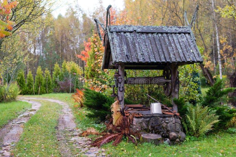 Puits historique avec une cour en bois de ferme de toit photos stock