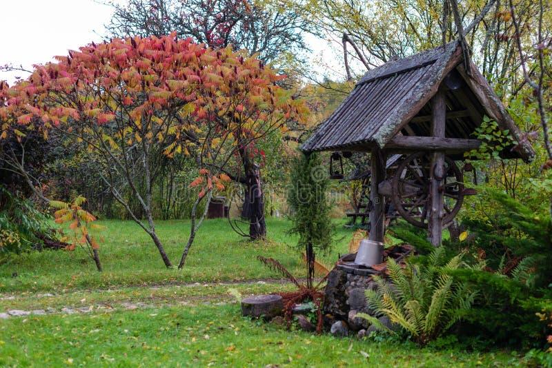Puits historique avec une cour en bois de ferme de toit photographie stock libre de droits