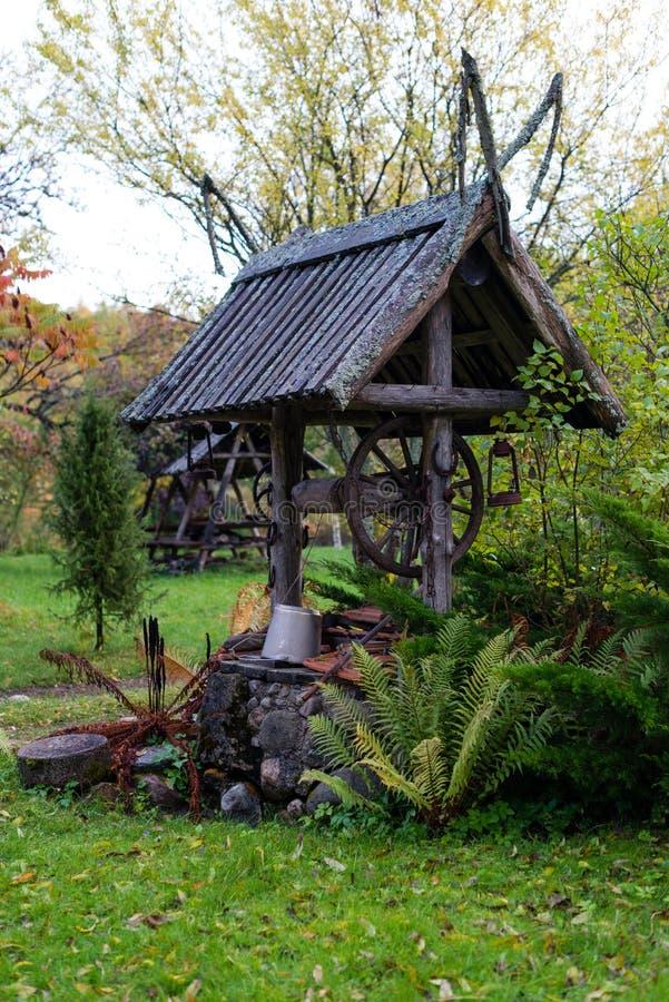 Puits historique avec une cour en bois de ferme de toit photographie stock