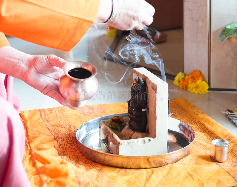 Puja to Lord Ganesh during the festival of Guru Purnima. Incense, water and fire are offered to purify the environment royalty free stock images