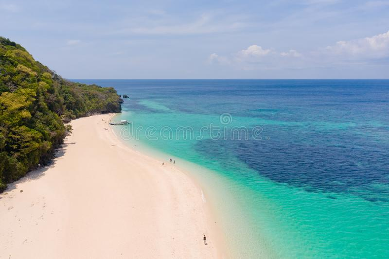 Puka Shell Beach. Wide tropical beach with white sand. Beautiful white beach and azure water on Boracay island, Philippines, top. View. Tourists relax on the stock photo