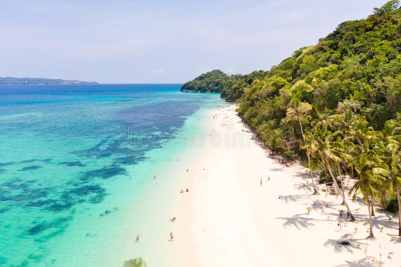 Puka Shell Beach. Wide tropical beach with white sand. Beautiful white beach and azure water on Boracay island, Philippines, top. View. Tourists relax on the stock images