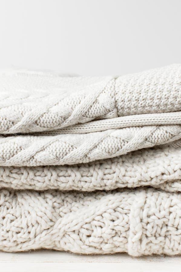 Pulôver de lã feito malha branco de duas camisetas em uma pilha na tabela de madeira no fundo claro A forma veste a ligação em po fotografia de stock