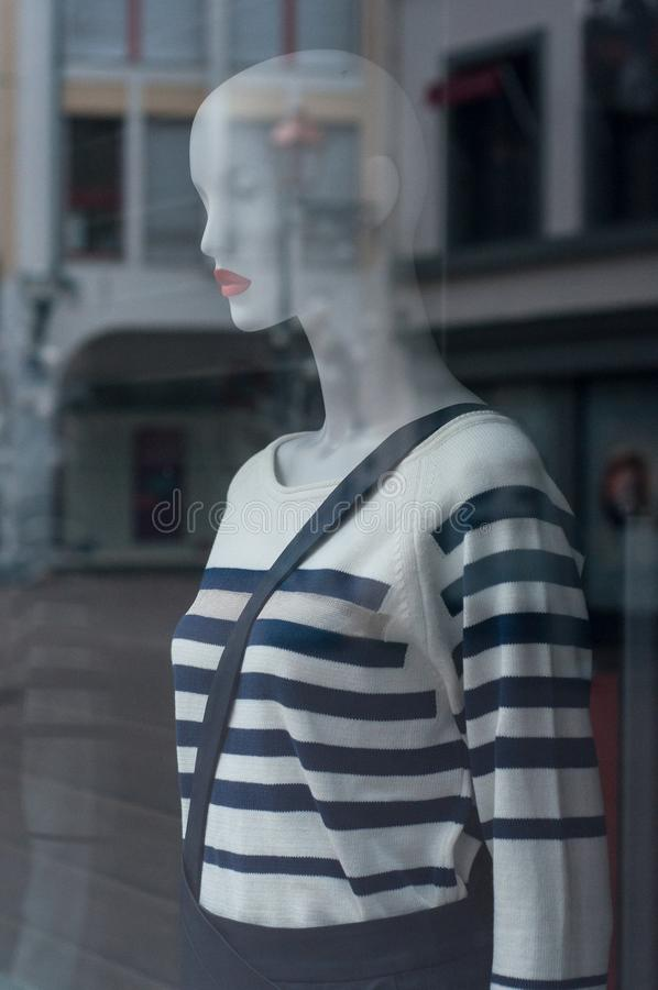 pulôver dos azuis marinhos das listras e revestimento do inverno no manequim na sala de exposições da loja da forma para mulheres foto de stock